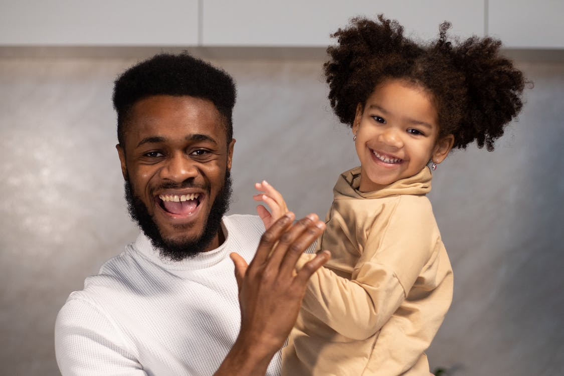 Positive young African American father with beard in casual clothes carrying smiling daughter and looking at camera