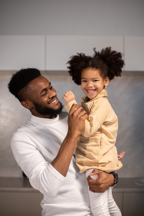 Delighted young African America father carrying adorable little daughter while having fun and looking at camera