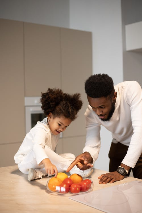 Glad young bearded African American father spending time with cute little daughter sitting on table with bowl of tasty ripe fruits in kitchen
