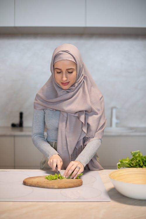 Focused Muslim woman cutting fresh salad on board