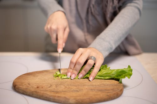 Crop unrecognizable housewife cutting fresh green salad with sharp knife on wooden chopping board while cooking in kitchen at home