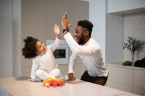 Joyful black father giving high five to adorable daughter