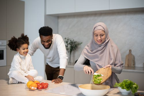 Cheerful young African American father and daughter looking at Muslim mother cutting green salad while cooking in kitchen at home
