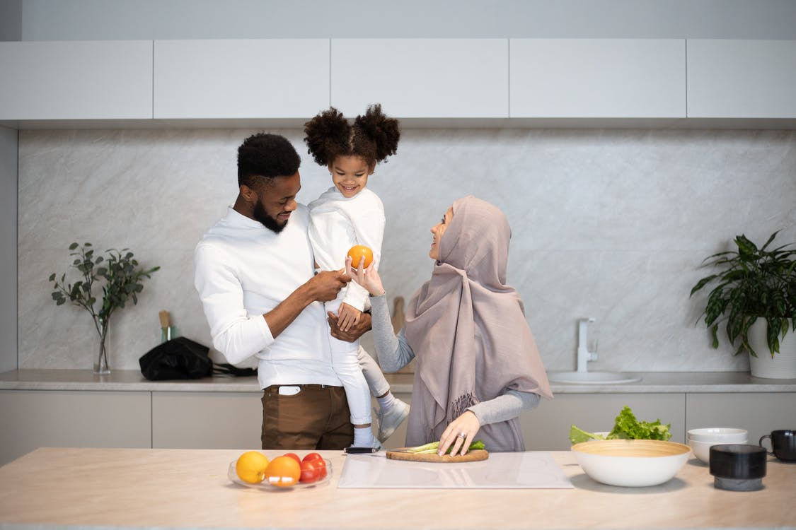 Happy young multiracial family in casual outfits standing near table in kitchen while cooking together at home