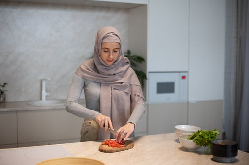 Concentrated Muslim housewife in hijab cutting tomato on chopping board while cooking in kitchen at home