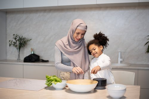 Happy diverse mother and daughter cooking together