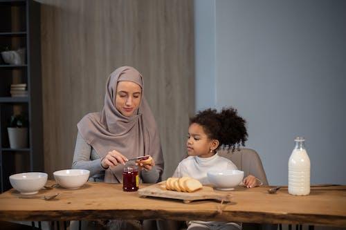 Wanita Berjilbab Coklat Duduk Di Samping Gadis Dengan Hijab Abu Abu