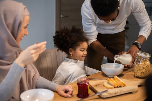 Cheerful diverse family having breakfast with milk and cereals