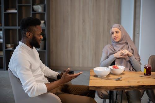 Homme En Thobe Blanc Assis à Côté D'une Femme En Hijab Blanc