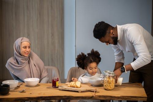 Glad family having breakfast at table