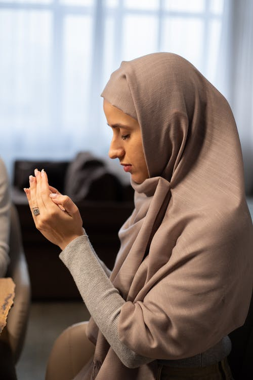 Side view of thoughtful young Muslim woman in hijab sitting on chair at table and praying before eating at home