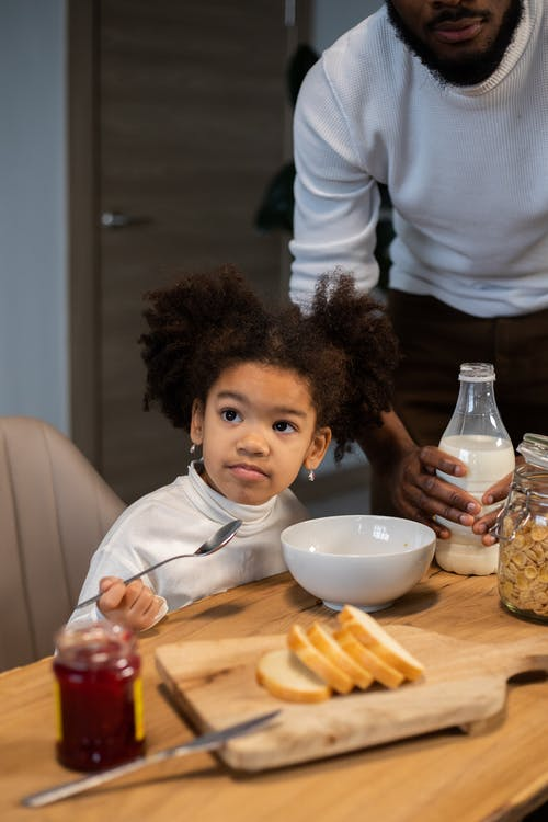 From above of crop African American bearded father and adorable little daughter having breakfast with milk and cornflakes at home