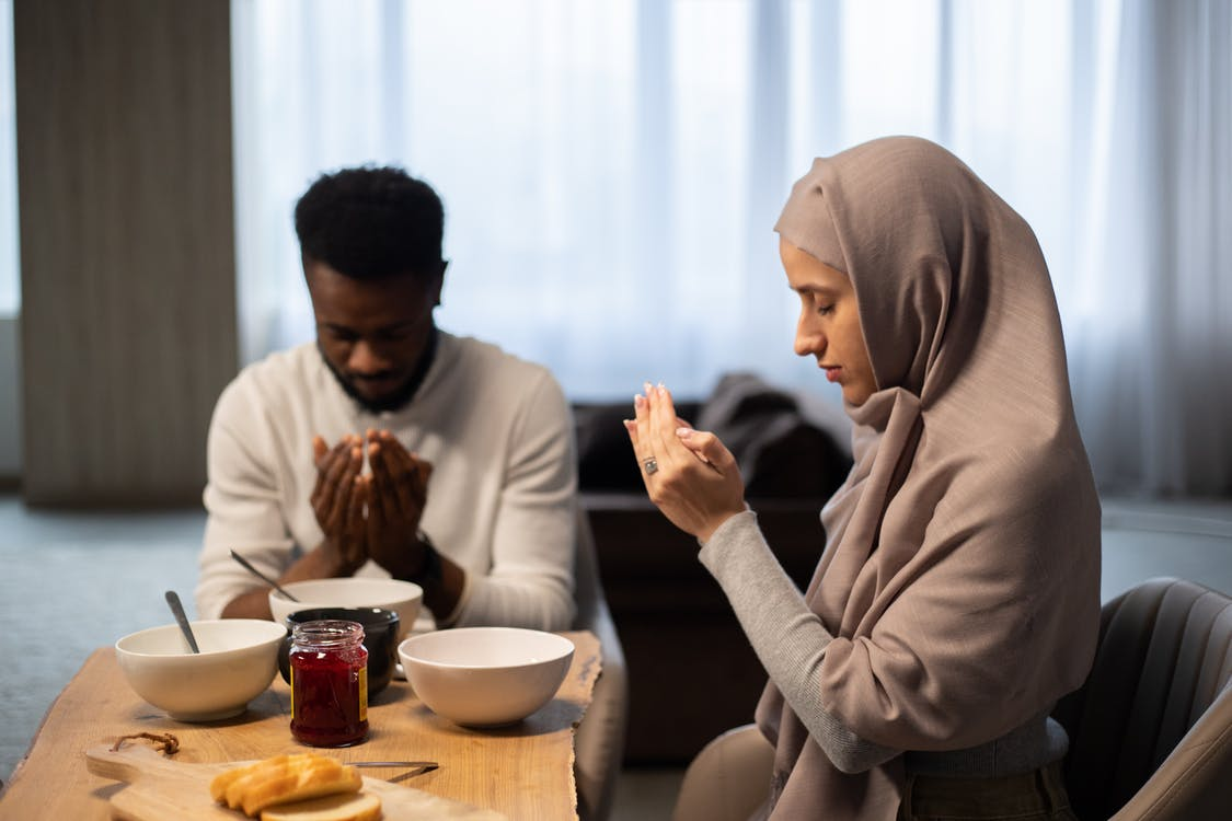Multiethnic couple praying at table before eating