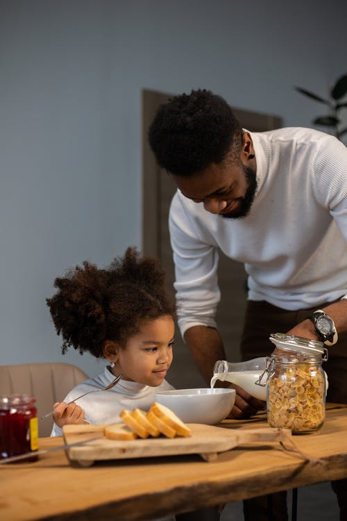 Happy young African American father pouring milk into bowl for daughter for eating cornflakes while having breakfast together at home