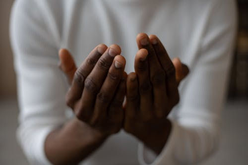 Crop black man praying at home