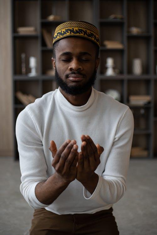 Focused Muslim black man praying at home
