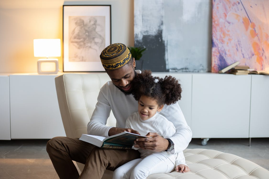 Positive young African American father in hat reading book to cute little daughter sitting on armchair at home