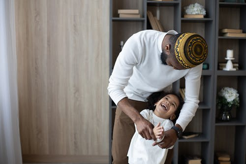Cheerful black father having fun with cute daughter