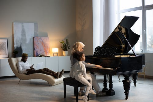 Full body focused young African American male sitting on armchair with smartphone and laptop while Muslim mother in hijab playing piano with adorable little daughter