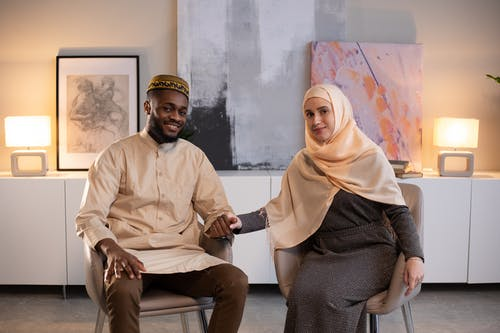 Man in White Thobe Sitting Beside Woman in Brown Hijab