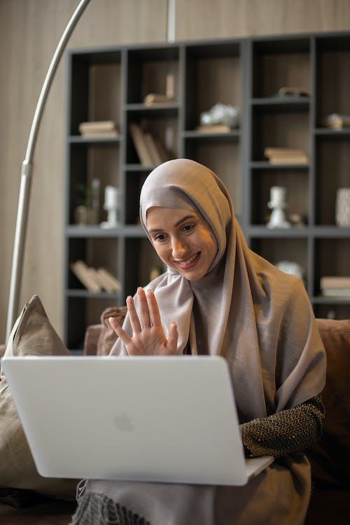 Woman in Brown Hijab Using White Laptop Computer