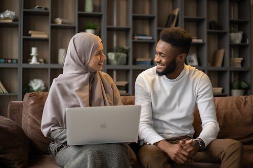Man in White Long Sleeve Shirt Sitting Beside Woman in Brown Hijab