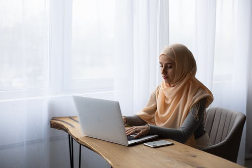 Busy Muslim lady working on laptop in light room