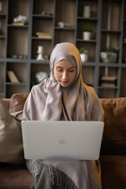 Independent Muslim female freelancer using laptop while sitting on couch