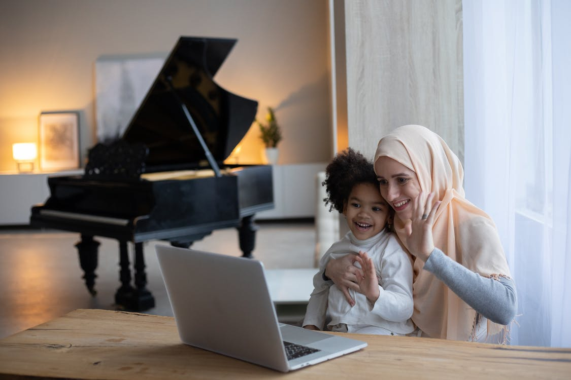 Positive Muslim mother and adorable African American girl sitting at table near window and having video call on portable laptop
