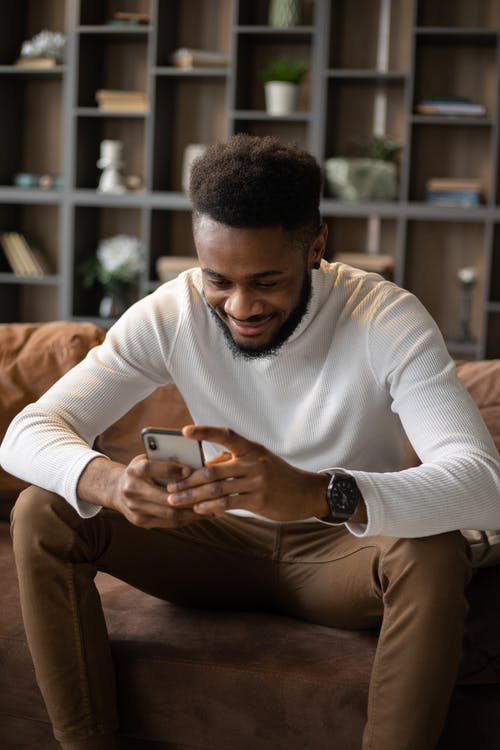 Positive black man using smartphone while sitting on sofa
