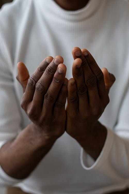 Selective focus of crop anonymous African American man wearing white turtleneck praying with open hands