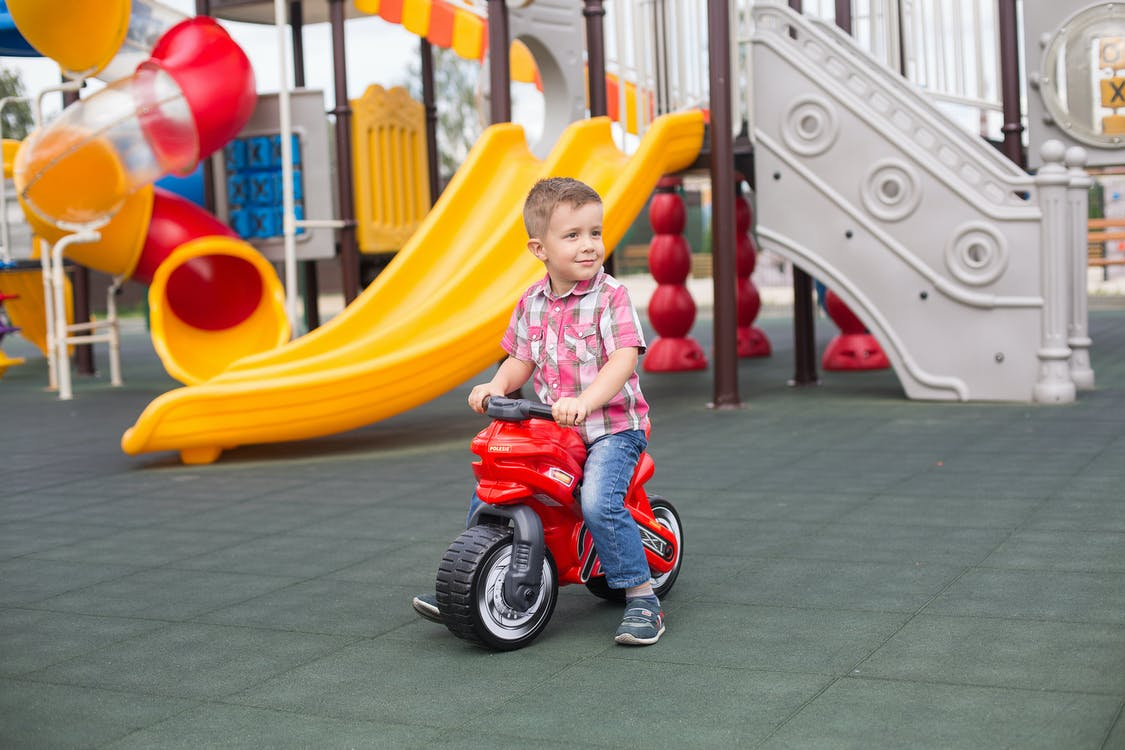 Girl in Pink Shirt Riding on Red and White Trike