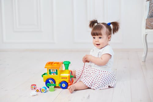 Baby Girl Sitting on the Floor Playing with the Toy Car