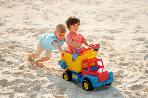 Two Boys Playing with a Toy Truck on Sand