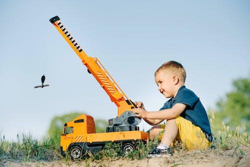 A Boy Sitting on Ground Playing Crane Truck Toy