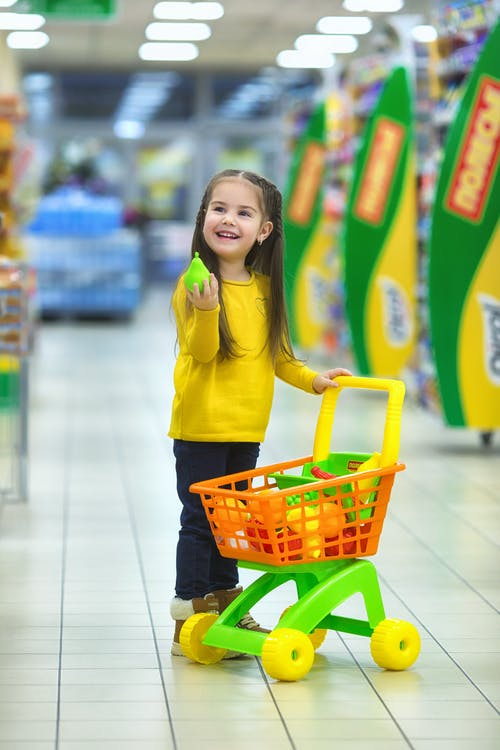 Girl in Yellow Long Sleeve Shirt and Black Pants Holding Red Shopping Cart