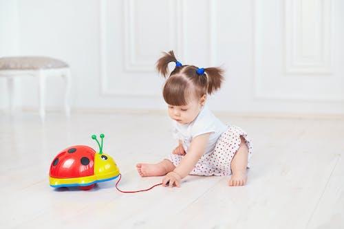 Girl in White and Red Polka Dot Dress Sitting on Floor