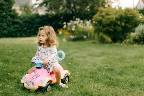Girl in White and Blue Floral Dress Riding on Blue and White Ride on Toy Car