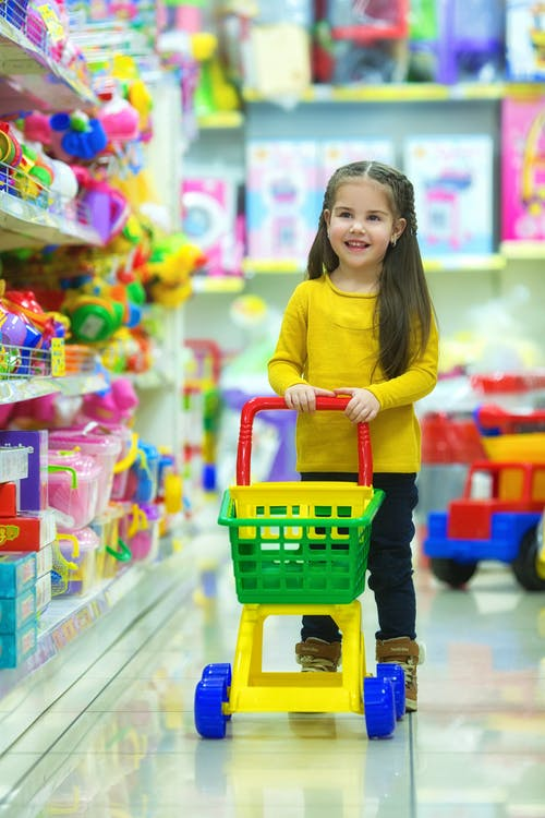 Girl in Yellow Long Sleeve Shirt Standing on Green Plastic Shopping Cart