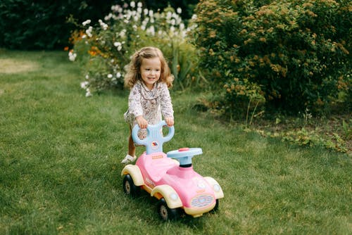 Girl in White and Pink Floral Dress Riding Pink and White Ride on Toy Car