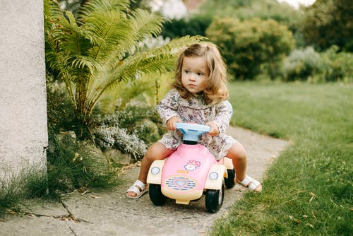 Girl in White and Blue Floral Dress Riding Blue and White Ride on Toy Car