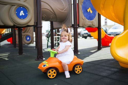 Girl in White Shirt Riding Yellow and Orange Ride on Toy