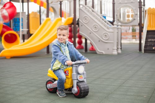 Child in Blue and White Jacket Riding Blue and White Trike