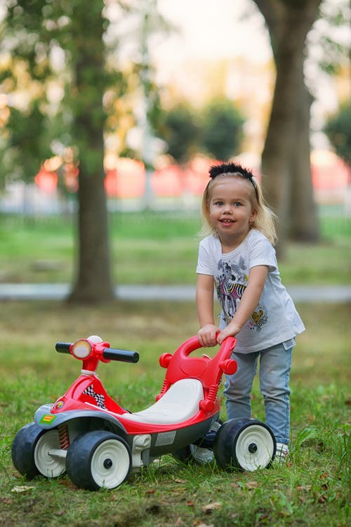 Girl in White T-shirt Riding Red and White Trike