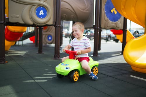 Child Riding on Green and Red Ride on Toy Car