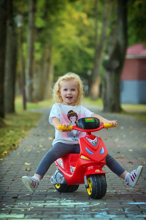 Girl Riding on Red and Black Bicycle