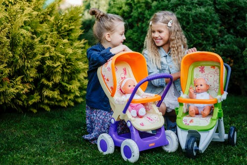 Girl in Blue Jacket Riding Pink and Purple Ride on Toy