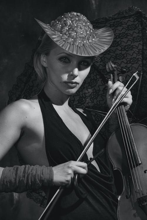 Woman in Black Tank Top and Hat with Flowers Holding Violin
