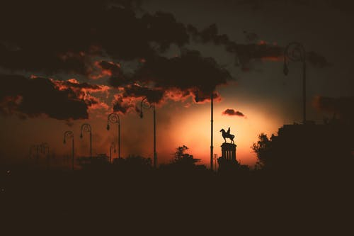 Silhouette of equestrian statue under cloudy sky at sunset