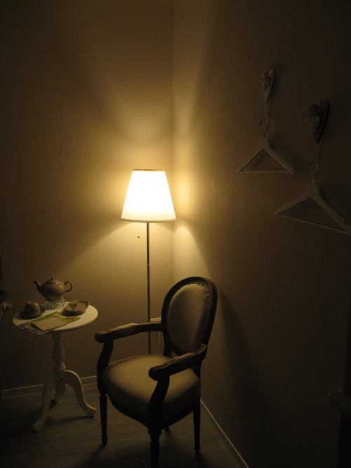 White Chair Beside Turned On Lamp and Round Coffee Table in the Corner of the Room